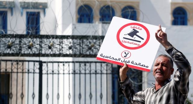 """A demonstrator shout slogans during a demonstration against a bill that would protect those accused of corruption from prosecution in front of Assembly of the Representatives of the People headquarters in Tunis, Tunisia September 13, 2017. The sign reads: """"No. We will not forgive."""" Credit: Reuters/Zoubeir Souissi"""