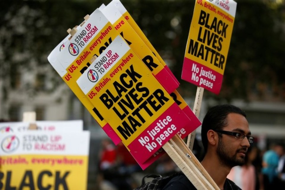 "A supporter of the UK branch of ""Black Lives Matter"" hands out placards at the start of a demonstration in London, Britain August 5, 2016. Credit: Reuters"