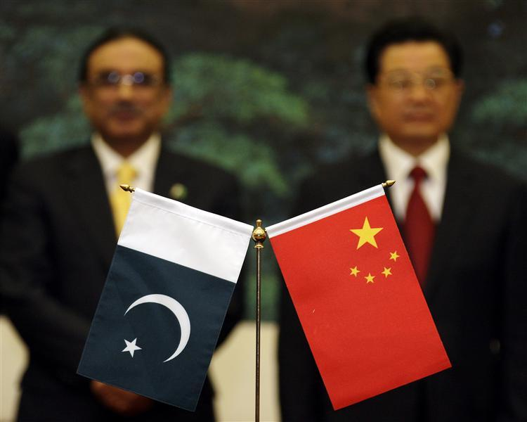 "Chinese President Hu Jintao (R) and his Pakistani counterpart Asif Ali Zardari stand near their respective country's flags during a signing ceremony at the Great Hall of the People in Beijing October 15, 2008. Zardari arrived on Tuesday for his first visit to China as president, and has said he wants his four-day trip ""to remind the leadership of the world how close our relationship is"". Pakistan is set to usher in a series of agreements with China during the trip, highlighting Islamabad's hopes that Beijing will help it through economic and diplomatic troubles. Credit: Reuters"