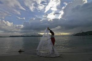 A fisherman arranges his fishing net at a beach in Kochi June 5, 2014. Credit: Reuters/Sivaram V/Files