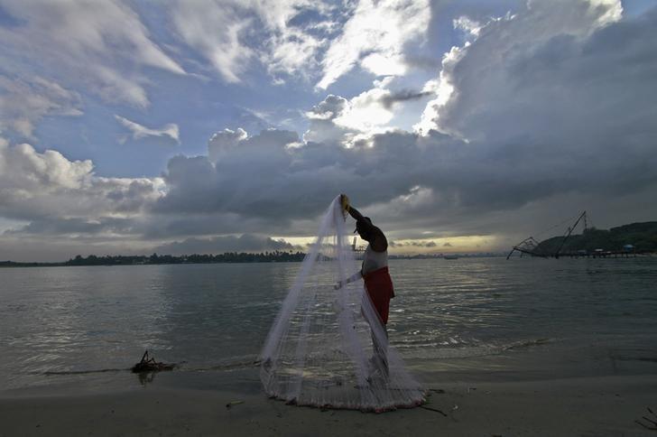 A fisherman arranges his fishing net at a beach in Kochi June 5, 2014. Credit: Reuters/Sivaram V/Files