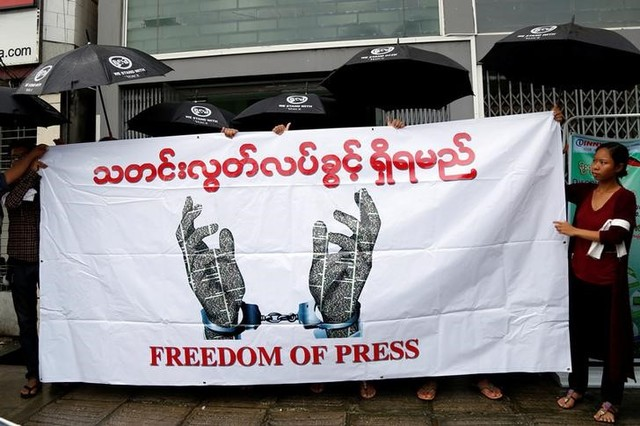 Journalists hold a banner as they protest against a law they say curbs free speech, at the start of a trial of two journalists who the army is suing for defamation over a satirical article, in Yangon, Myanmar June 8, 2017. Credit:Reuters