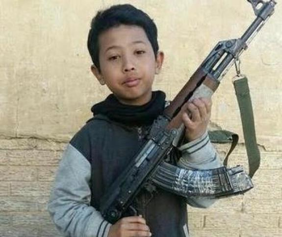 Hatf Saiful Rasul, an Indonesian boy and son of convicted militant Syaiful Anam, aka Brekele, holds a rifle during his time fighting in Syria with Islamic State before his death on September 1, 2016 aged 12 in this picture released through Telegram. Credit: Reuters