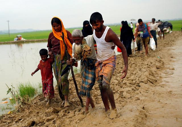 Rohingya refugees walk on the muddy path after crossing the Bangladesh-Myanmar border in Teknaf, Bangladesh, September 3, 2017. Credit;Reuters