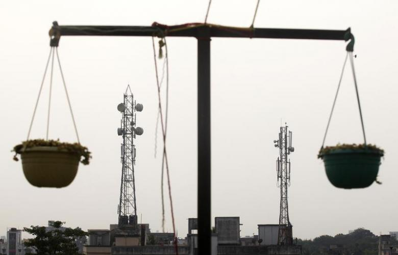 Telecommunication towers are pictured through hanging flower pots at a residential building in Kolkata December 11, 2012. Credit: Reuters/Rupak De Chowdhuri/Files