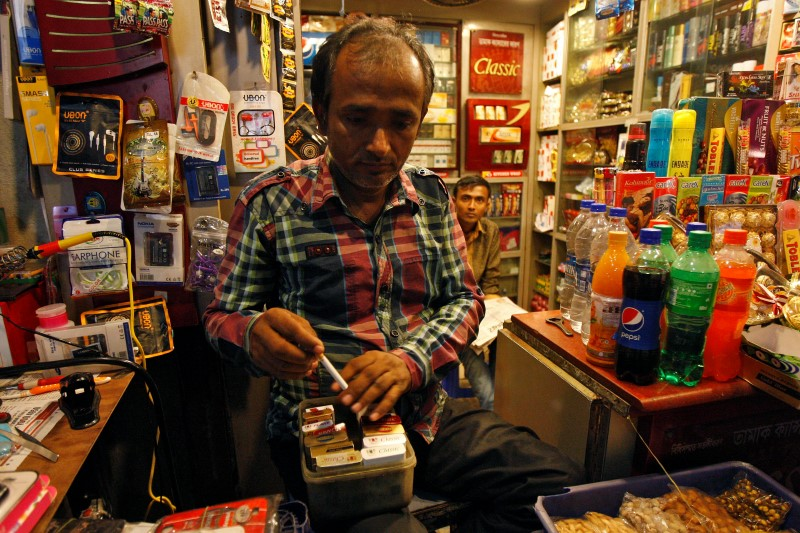 A shopkeeper takes out a cigarette from a box for a customer in Kolkata October 15, 2014. Credit: Reuters/Rupak De Chowdhuri