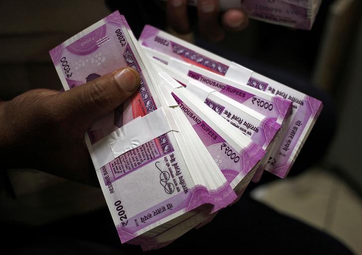 A cashier displays the new 2000 Indian rupee banknotes inside a bank in Jammu, November 15, 2016. Credit: Reuters/Mukesh Gupta/File photo
