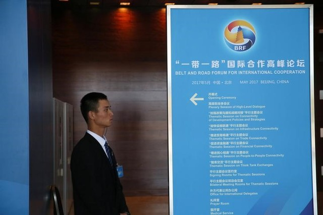 A staff member stands next to a sign for the Belt and Road Forum at the National Convention Centre in Beijing, China May 13, 2017. Credit: Reuters/Stringer/Files