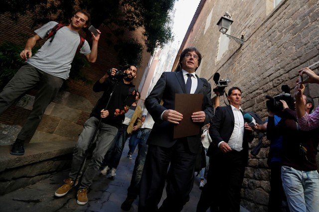 Catalan President Carles Puigdemont is surrounded by media as he leaves the regional government headquarters after delivering a statement in Barcelona, Spain, October 26, 2017. Credit: Reuters/Yves Herman