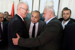 Palestinian Prime Minister Rami Hamdallah (L) shakes hands with Hamas Chief Ismail Haniyeh in Gaza City October 2, 2017. Credit: Reuters