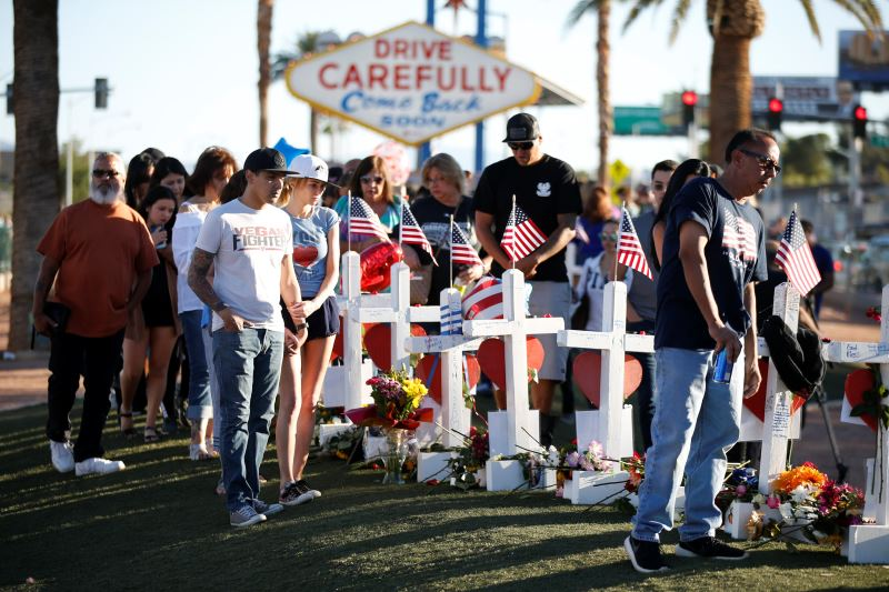 People gather to look at white crosses set up for the victims of the Route 91 Harvest music festival mass shooting in Las Vegas, Nevada, US, October 6, 2017. Credit: Reuters/Chris Wattie