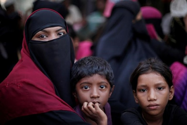 A Rohingya refugee family sits in a queue as they wait to receive humanitarian aid at Kutupalong refugee camp near Cox's Bazar, Bangladesh October 24, 2017. Credit: Reuters