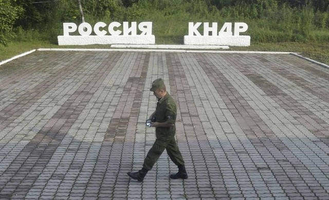 "A guard walks along a platform past signs, which read ""Russia"" (L) and ""DPRK""(Democratic People's Republic of Korea), at the border crossing between Russia and North Korea in the settlement of Tumangan, North Korea July 18, 2014. Credit: Reuters"