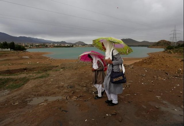 Afghan school girls hold umbrellas to shelter from rain on outskirt of Kabul, Afghanistan May 15, 2017. Credit: Reuters