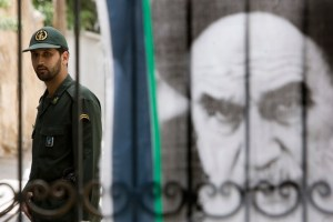 A member of the Iranian Revolutionary Guard Corps stands next to a picture of the Ayatollah. Credit: Reuters