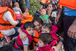 A Syrian mother cries with relief as she embraces her three young children after a rough sea crossing. Credit: UNHCR/Ivor Prickett