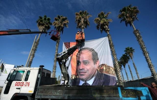 Palestinians hang a poster depicting Egypt's President Abdel Fattah al-Sisi at Rafah border crossing with Egypt, in the southern Gaza Strip November 1, 2017. Credit: Reuters/Ibraheem Abu Mustafa