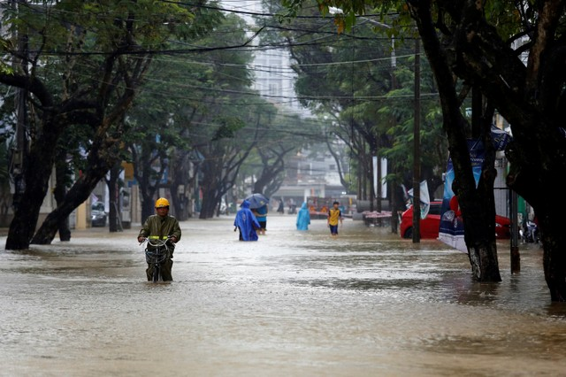 People go along flooded road after typhoon Damrey hits Vietnam in Hue city, Vietnam November 5, 2017. Credit: Reuters/Kham