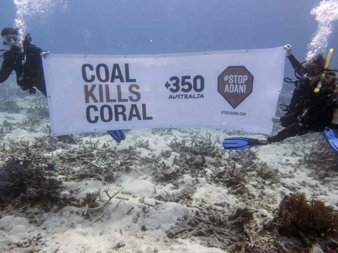 Protesters hold a 'coal kills coral' banner underwater at the Great Barrier Reef. Credit: StopAdaniAlliance.