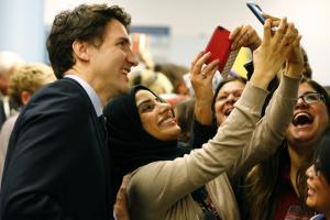 Canada's Prime Minister Justin Trudeau (L) poses with airport staff as they await Syrian refugees to arrive at the Toronto Pearson International Airport in Mississauga, Ontario, December 10, 2015. After months of promises and weeks of preparation, the first planeload of Syrian refugees was headed to Canada on Thursday, aboard a military plane to be met at Toronto's airport by Trudeau. Credit: Reuters/Mark Blinch