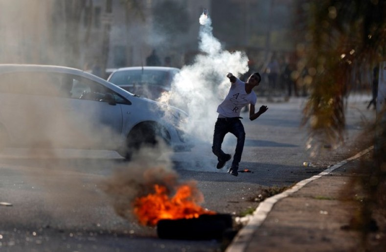 A Palestinian protester hurls back a tear gas canister fired by Israeli troops during clashes in the West Bank village of Qusrah near Nablus, November 30, 2017. Credit: Reuters/Mohamad Torokman