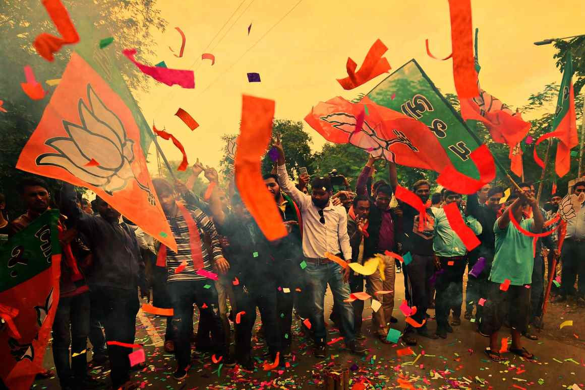 BJP workers burst firecrackers to celebrate their victory in the assembly elections, at the party office 'Kamlam' in Gandhinagar on Monday. Credit: PTI/Santosh Hirlekar