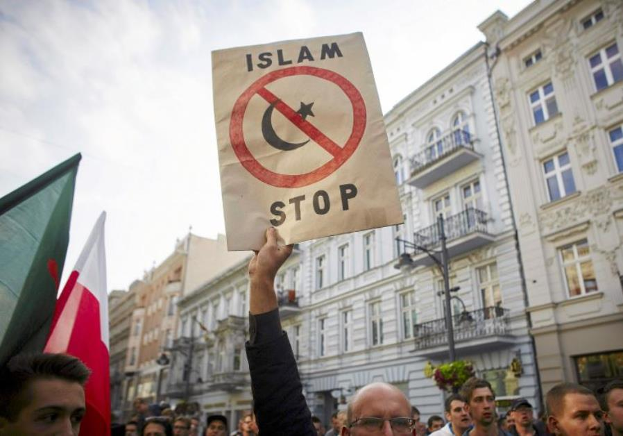 """A protester from a far-right organization holds up a sign which reads """"Islam Stop"""" during a protest against refugees in Lodz, Poland. Credit: Reuters"""