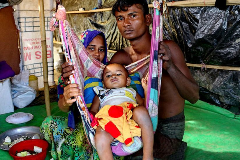 A Rohingya couple, Mohammad Faisal and his wife Hajera, pose for a photo with their child at their camp at Teknaf Nature's Park, Bangladesh. Credit: Farid Ahmed/IPS