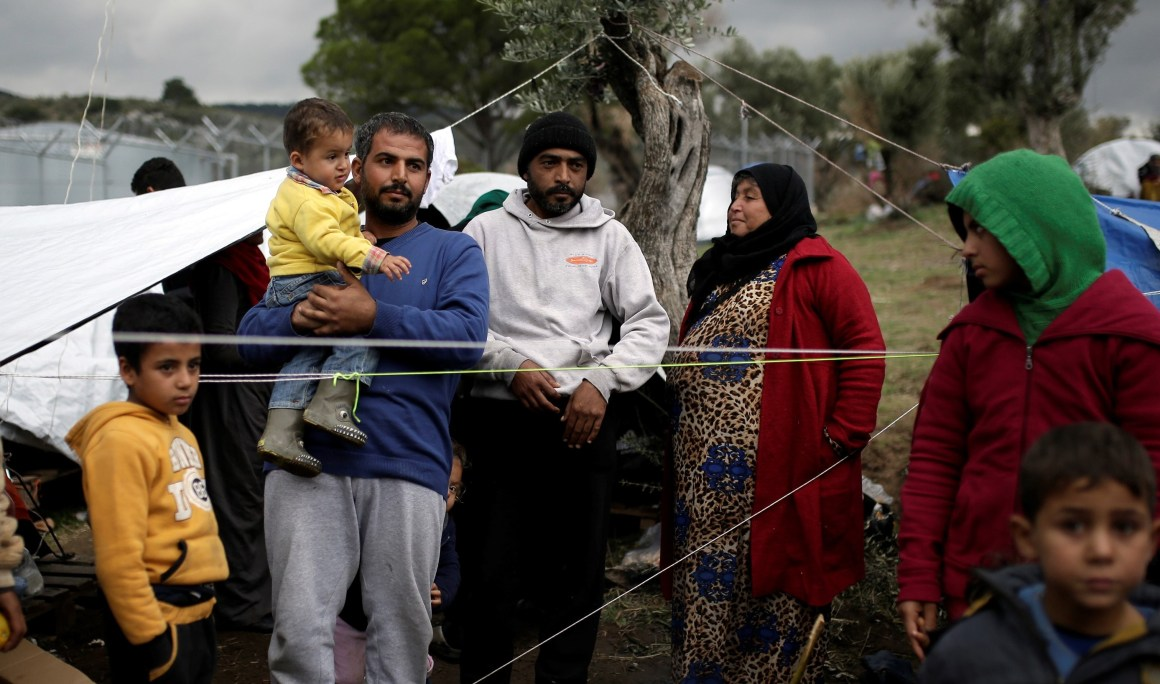 Syrian refugee Bashar Wakaa (3rd L) and his family stand in front of their tents at a makeshift camp for refugees and migrants next to the Moria camp on the island of Lesbos, Greece, November 30, 2017. Credit: Reuters/Alkis Konstantinidis