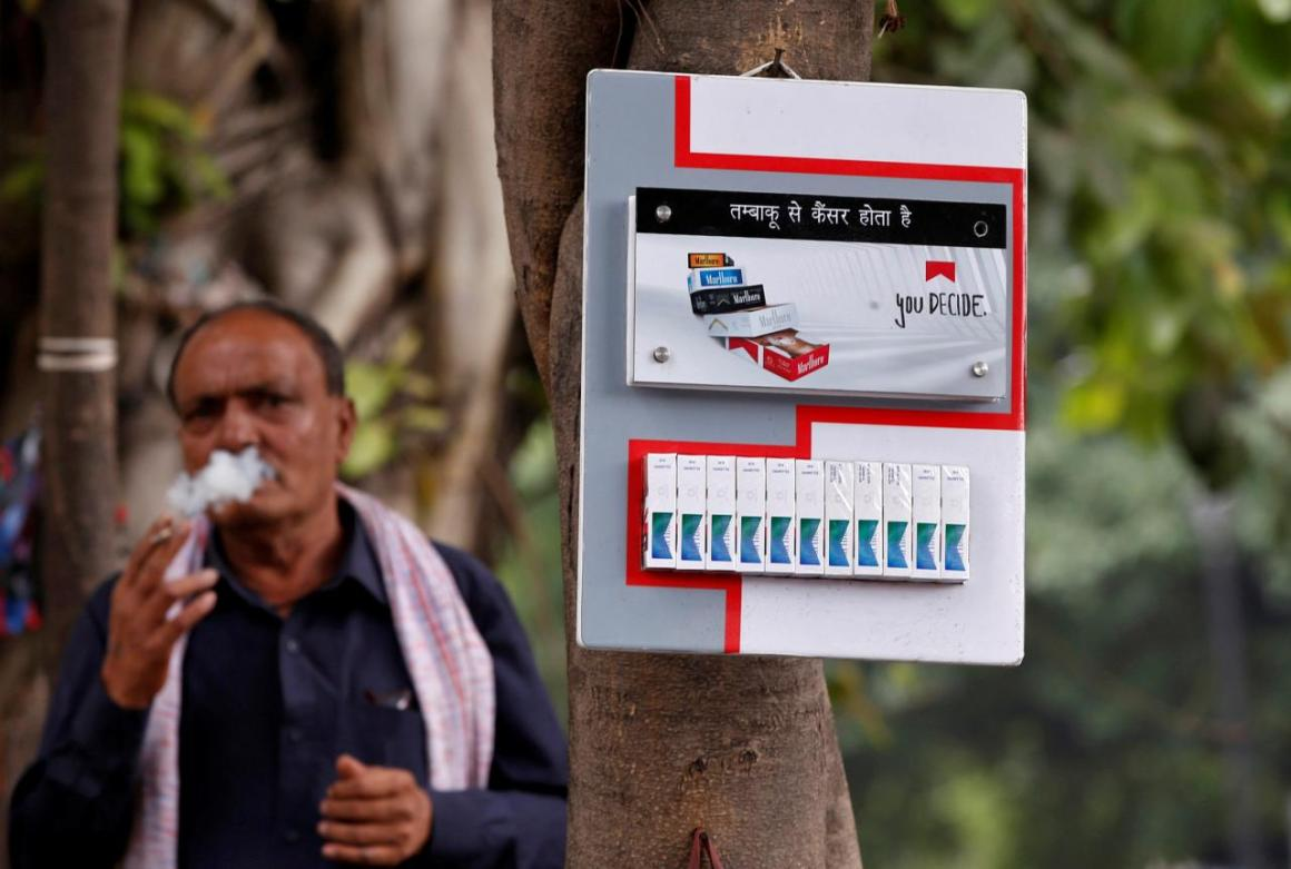 A man smokes next to a cigarette advertisement hung on a tree at a marketplace in New Delhi, India, May 3, 2017. Credit: Reuters/Adnan Abidi