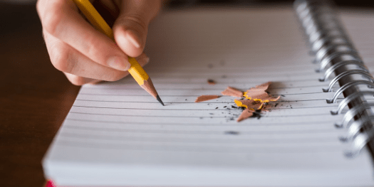 Homeschooler writing in a notebook with a pencil - Online Writing Classes
