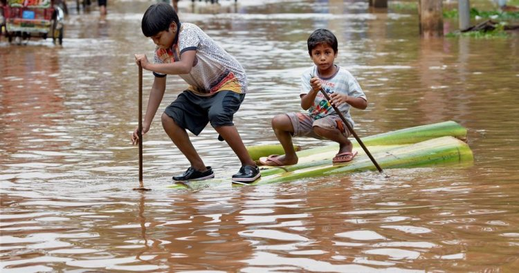 Guwahati: Two boys crossing a flooded street on a raft made of banana tree trunk n Guwahati on Wednesday. The floods have claimed four lives so far in last 24 hours. PTI Photo(PTI6 14 2017 000046B)