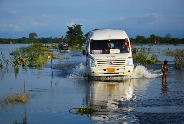 Kamrup : People travel in a mini bus at flood-hit Jamlai village in Kamrup district of Assam on Thursday. PTI Photo (PTI7_14_2017_000222B)