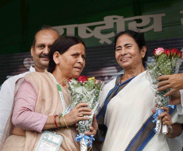 Patna:  RJD senior leader Rabri Devi greets West Bengal Chief Minister Mamata Banerjee during the  'BJP bhagao, desh bachao' rally at Gandhi Maidan in Patna on Sunday. PTI Photo(PTI8_27_2017_000097B) *** Local Caption ***