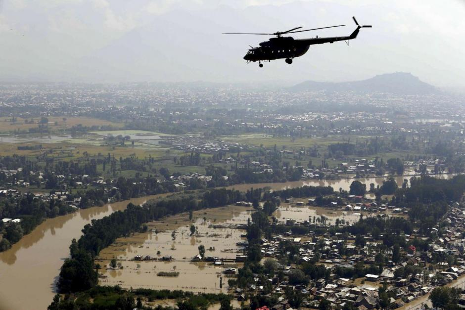 An Indian Air Force helicopter flies above flooded-affected areas of Kashmir region September 13, 2014. REUTERS/India's Press Information Bureau/Handout via Reuters