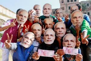 Jammu : Children wear Prime Minister Narendra Modi's mask and display new currency 2000 note as they welcome the demonetisation step in Jammu on Sunday. PTI Photo   (PTI11_13_2016_000190B)