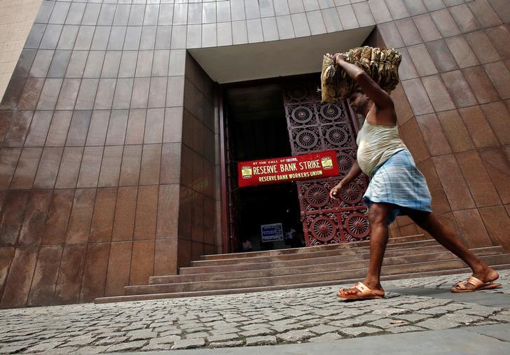 A labourer carrying dry leaves walks past a Reserve Bank of India (RBI) building during a nationwide strike in Kolkata, India September 2, 2016. REUTERS/Rupak De Chowdhuri/File Photo