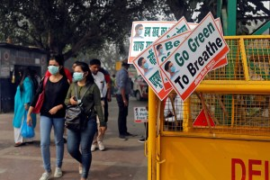 Women wearing masks walk past a road barrier on a smoggy day in New Delhi, India, November 9, 2017. REUTERS/Saumya Khandelwal