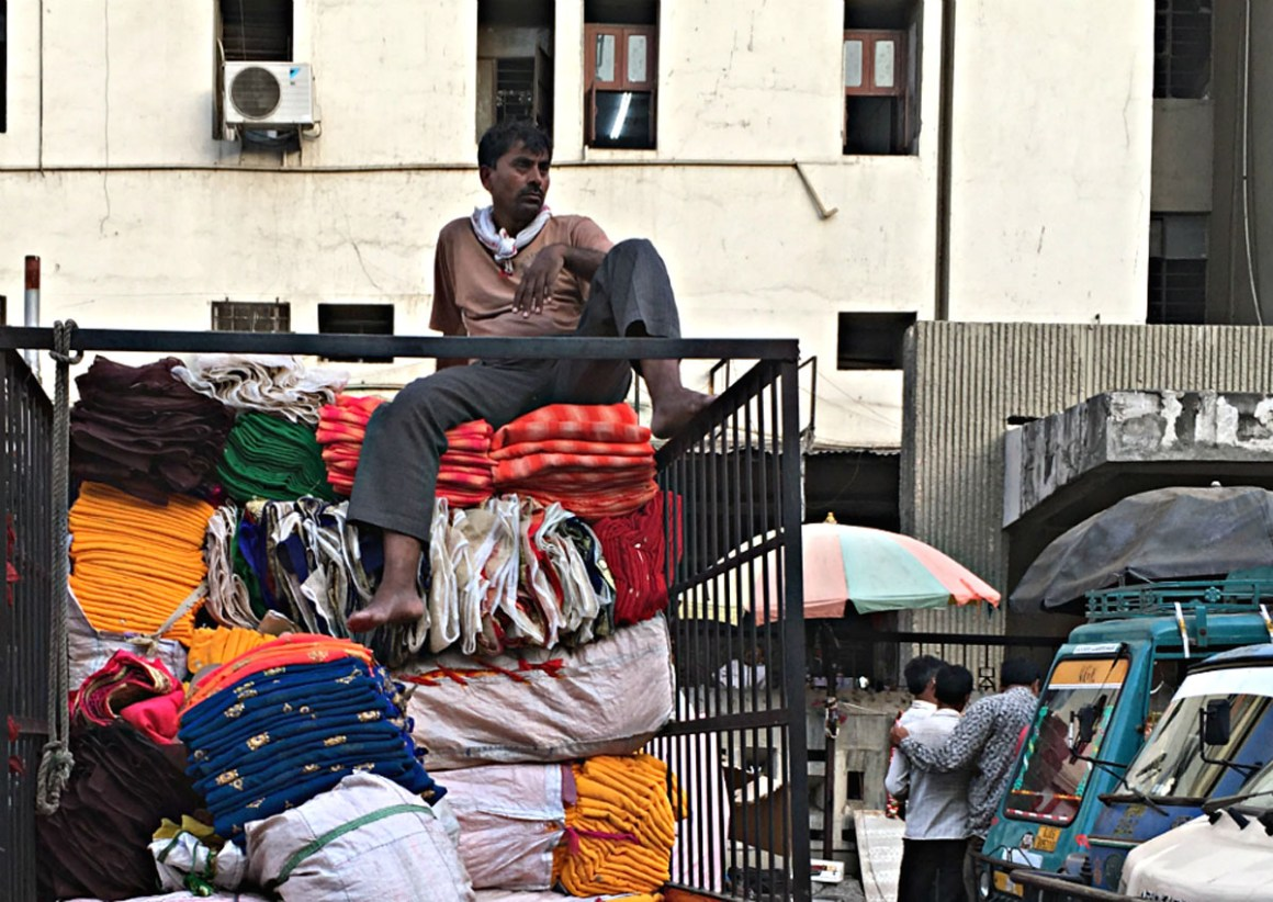 A man rests on a pile of fabric in the textile market of Surat, a key textile hub of India and the largest manufacturer of synthetic fabric in the country. India exports $6 billion worth of synthetic fabric annually. THOMSON REUTERS FOUNDATION/Roli Srivastava