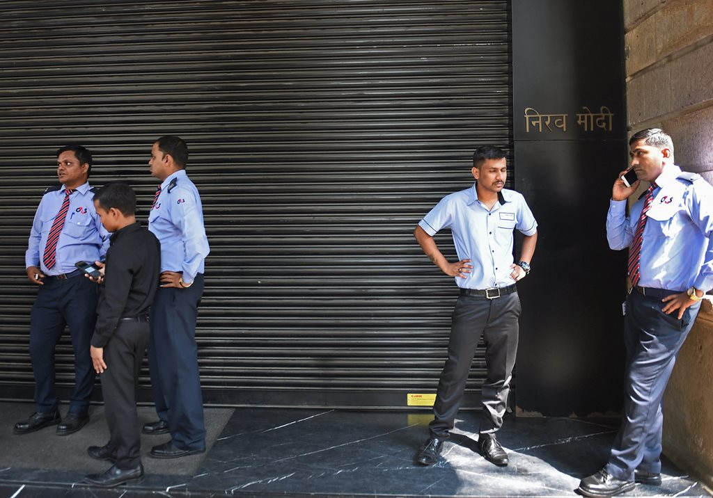 Mumbai: Security guards wait outside the showroom of Nirav Modi as Enforcement Directorate team raids his showroom and office at Kala Ghoda in Mumbai on Thursday. PTI Photo by Shashank Parade(PTI2_15_2018_000057B)