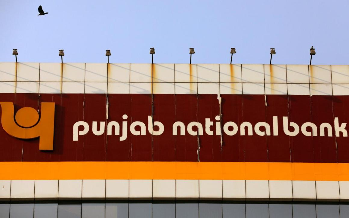 A bird flies past the logo of Punjab National Bank installed on the facade of its office in Mumbai, India February 21, 2018. REUTERS/Danish Siddiqui
