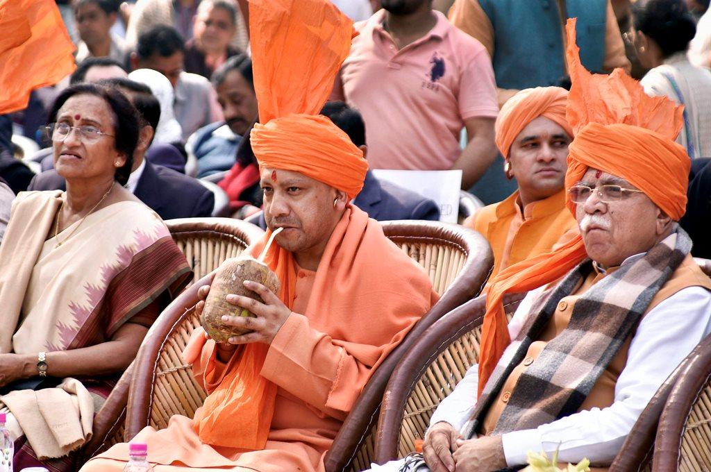 Faridabad: Uttar Pradesh Chief Minister Yogi Adityanath drinks coconut water during Surajkund International Crafts Mela in Faridabad on Friday. Also seen are Haryana Chief Minister Manohar Lal Khattar and UP Tourism Minister Rita Bahuguna Joshi. PTI Photo (PTI2_2_2018_000084B)