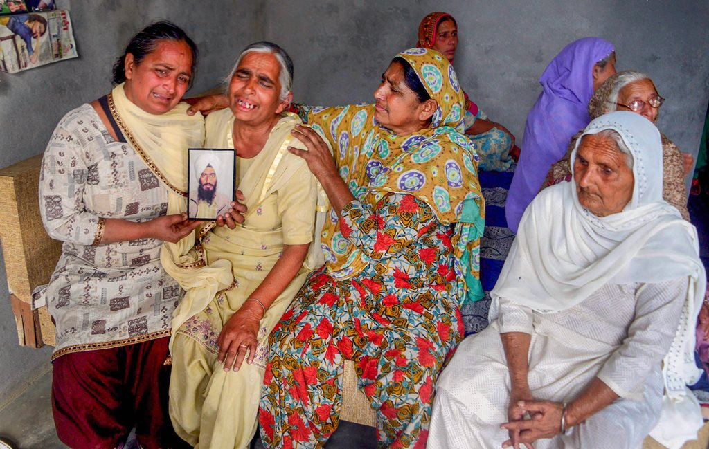 Amritsar: Family members grieve by a portrait of one of the 39 Indian workers feared killed in Iraq, on the outskirts of Amritsar on Tuesday. External Affairs Minister Sushma Swaraj in a statement made at Rajya Sabha today, stated that the 39 bodies exhumed from a mount in Badoosh in Iraq have been identified as those of abducted Indians and will be brought back to India on a special plane. PTI Photo(PTI3_20_2018_000168B)