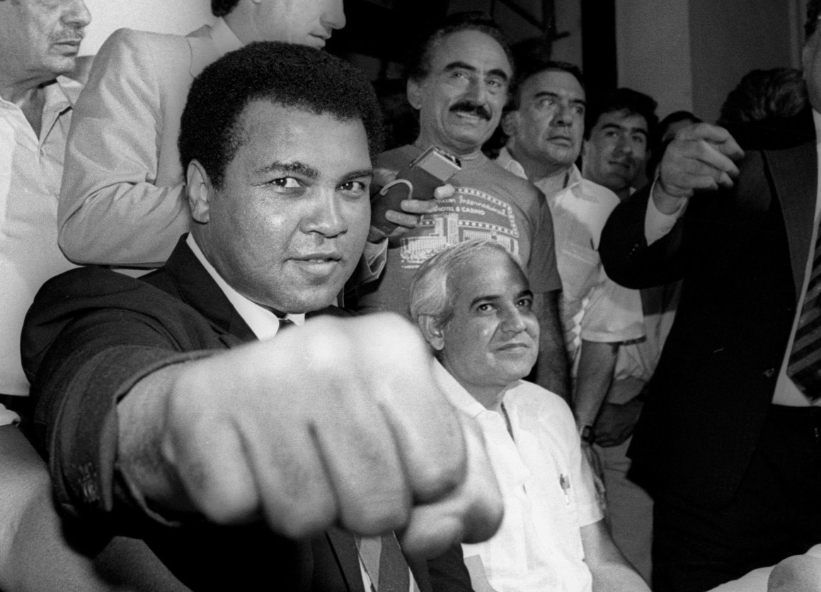 A smiling Muhammad Ali shows his fist to reporters during an impromptu press conference in Mexico City July 9, 1987. REUTERS/Jorge Nunez