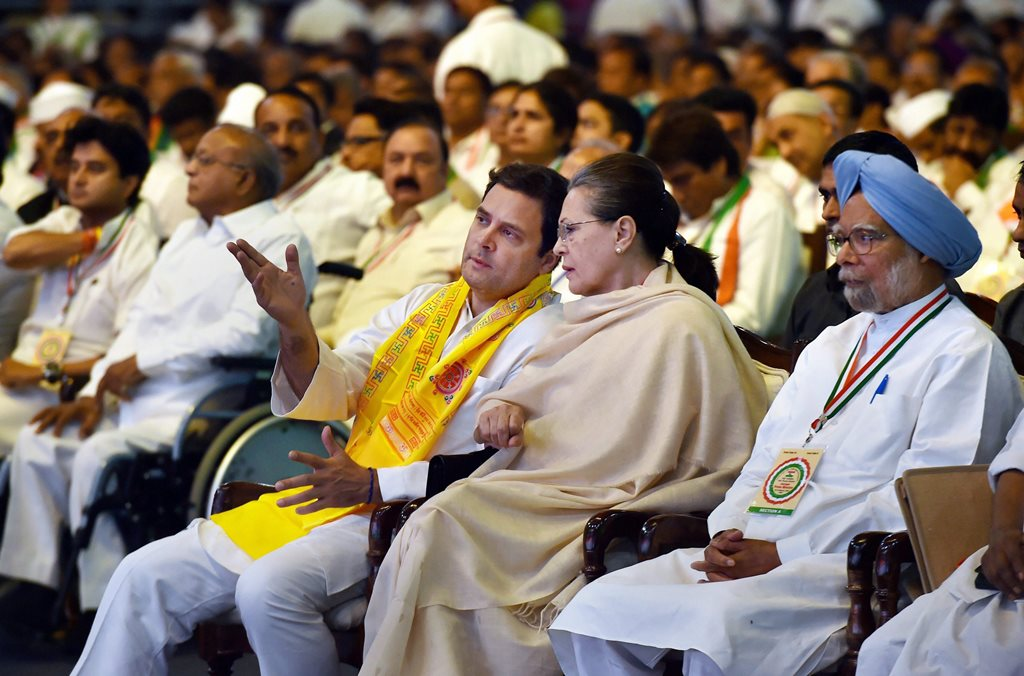 New Delhi: Chairperson CPP Sonia Gandhi and President Rahul Gandhi talk as former Prime Minister Manmohan Singh looks on, during the 84th Plenary Session of Indian National Congress (INC) at the Indira Gandhi Stadium in New Delhi on Saturday. PTI Photo by Manvender Vashist (PTI3_17_2018_000112B)