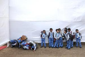 School children try to watch a cultural event through a temporary divider as others wait for their bus at a school in Mumbai January 30, 2014. REUTERS/Danish Siddiqui (INDIA - Tags: EDUCATION SOCIETY)
