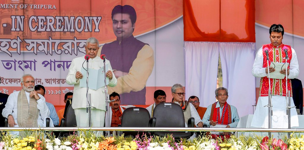 Agartala: Tripura BJP President Biplab Kumar Deb being sworn-in as the 10th chief minister of the state by Governor Tathagata Roy during a ceremony in Agartala on Friday. Prime Minister Narendra Modi is also seen on the stage. PTI Photo (PTI3 9 2018 000102B) *** Local Caption ***
