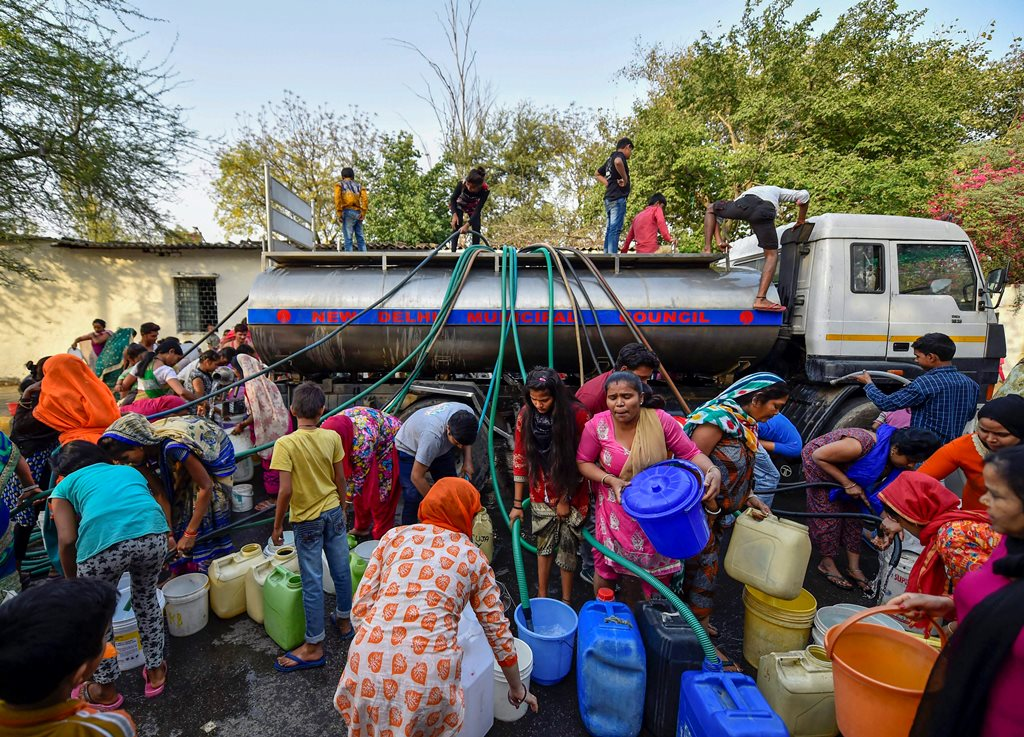 New Delhi: Residents of Vivekanand camp gather around a Municipal Corporation tanker to fill water, at Chanakyapuri in New Delhi, on Wednesday. According to the UN, the theme for World Water Day 2018, observed on March 22, is 'Nature for Water' – exploring nature-based solutions to the water challenges we face in the 21st century. PTI Photo by Ravi Choudhary (PTI3_21_2018_000124B)