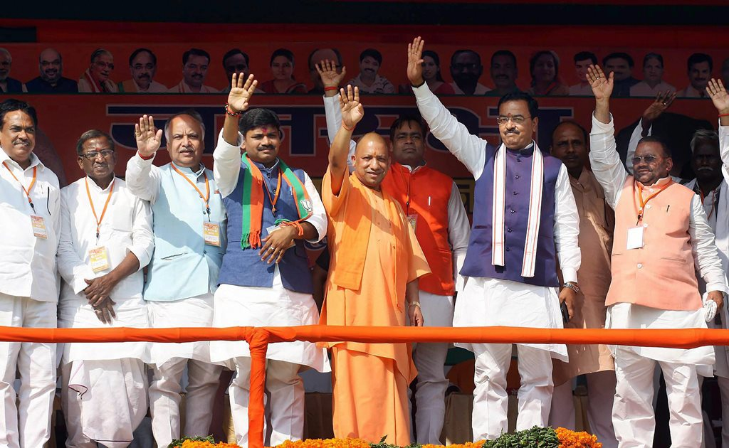 Nawabganj: UP Chief Minister Yogi Adityanath with Uttar Pradesh deputy chief minister Keshav Prasad Maurya and other BJP leaders wave to the gathering during a campaign ahead of Phulpur by-elections, at Nawabganj in Allahabad on Sunday. PTI Photo(PTI3_4_2018_000093B)