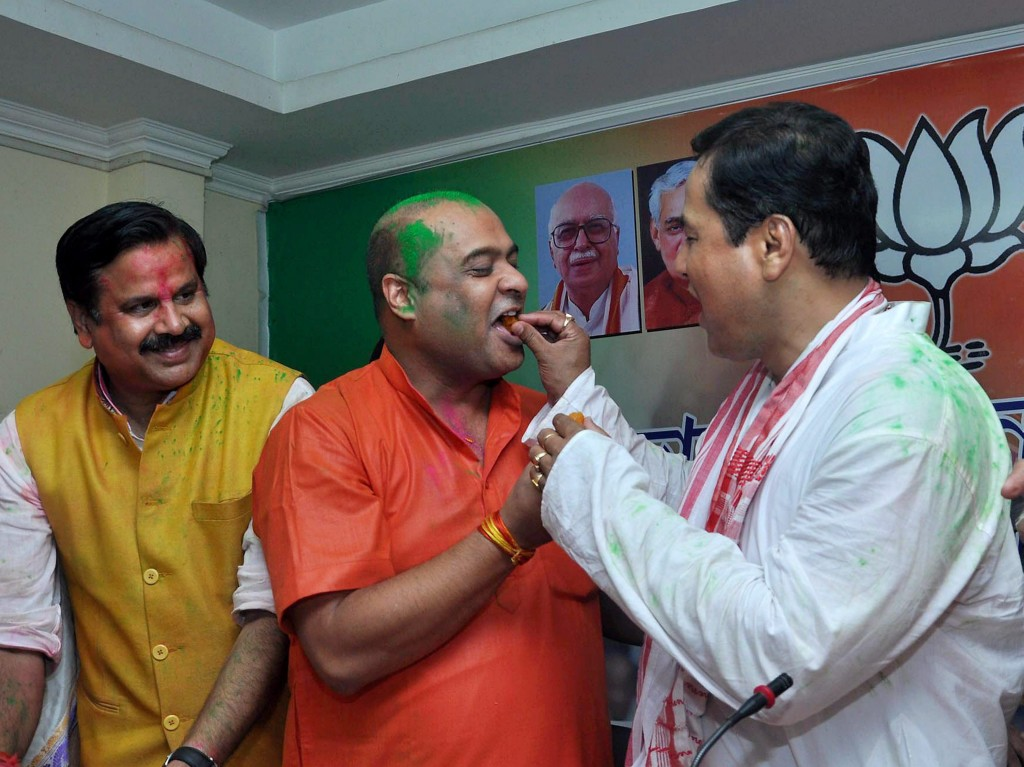 Guwahati: BJP chief ministerial candidate Sarbananda Sonowal exchanging sweets with party leader Himanta Biswa Sarma at a press conference after the party's thumping win the Assam Assembly polls, BJP Party head office in Guwahati on Thursday. PTI Photo (PTI5_19_2016_000363A)